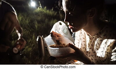 the woman is eating on the grass at night. Tourist trekking....