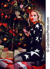 woman decorates a tree - Happy beautiful young woman is...