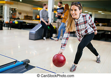 Beautiful woman bowling with friends getting ready to throw...