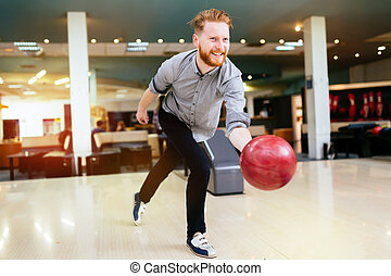 Handsome man bowling in club and throwing ball