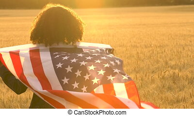 Girl teenager female young woman holding an American USA Stars and Stripes flag in a wheat field at sunset or sunrise