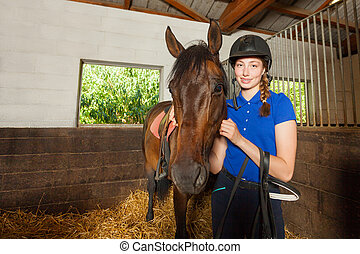 Female jockey standing in stable with bay horse