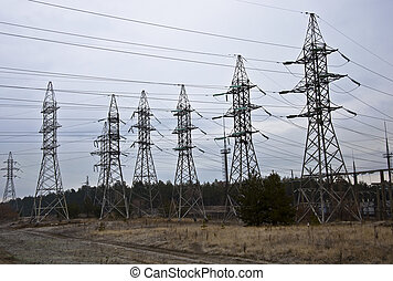Power transmission towers in the autumn forest. Overcast sky.