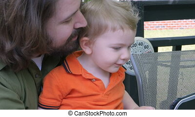 A father and son use a tablet together sharing app or video...