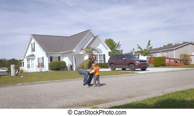 A father lovingly lifts his toddler son in the air on a street in suburbia