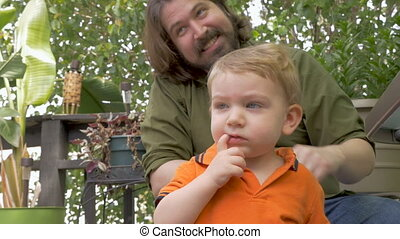 Young toddler child boy thinking with father sitting behind...