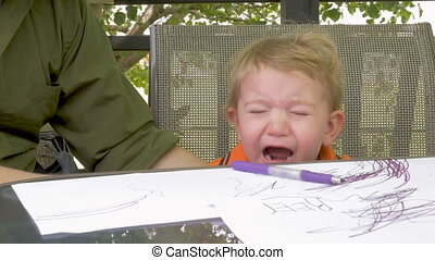 A tired crying toddler sitting at a table coloring - A tired...