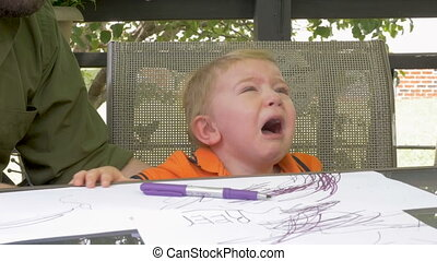 A father hands a marker to his crying frustrated young child boy in slow motion