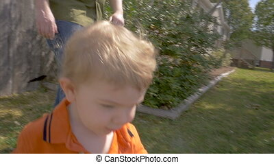 A cute toddler boy walking outside in sun light on green lawn with his father
