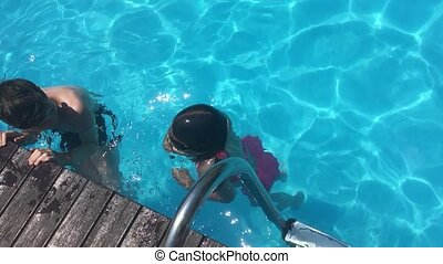 bathe in the pool water. children boy and girl swimming in...