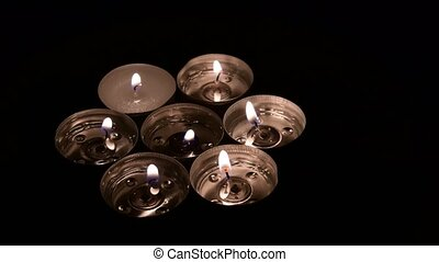 Tea candles rotation on a mirror background with camera moves from left side to the right. Closeup