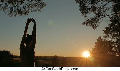Young woman stretching towards the sky in forest at sunset -...