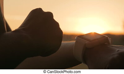 Woman using smartwatch in forest at sunset - Woman using...