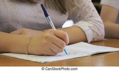 Schoolgirl writing text in exercise book. Close-up -...