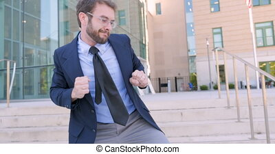 Crazy Businessman celebrating and silly dancing outside office building in 4k