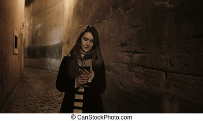 Young stylish woman going late at night through the deserted...