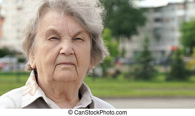 Portrait of serious old woman aged 80s outdoors