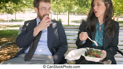 Two attractive young millennial business executives eating healthy food outside