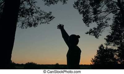 Young woman stretching towards the sky in the forest after...