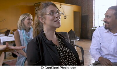 Group of attractive businesspeople sitting and talking at a meeting