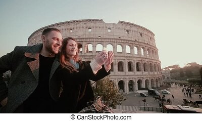 Happy young couple taking a selfie photo near the Colosseum...