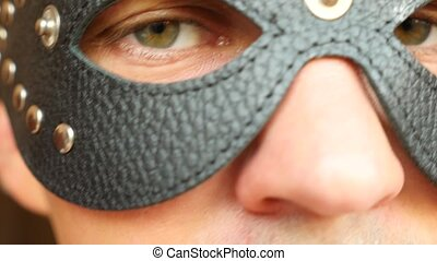 close-up leather black mask. green eyes look through the...