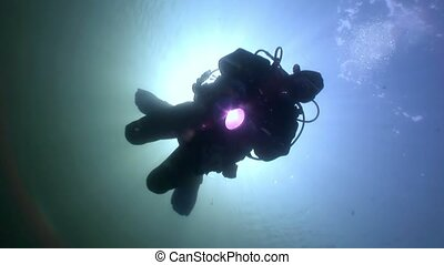 Scuba diver silhouette flashlight on background reflection...