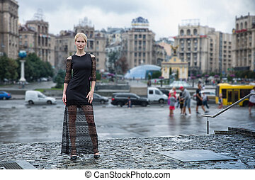 Blonde wooman dreesed in black dress in the city. Rainy day....