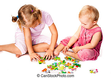 Children solving jigsaw puzzle isolated on white