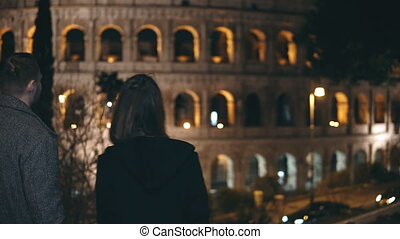 Young happy couple walking in the city of Rome, Italy near the Colosseum. Traveling man and woman enjoying the sight.