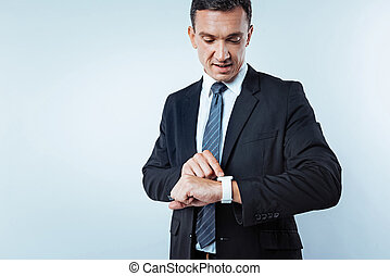 Busy male entrepreneur checking time over background - What...