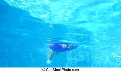 children swim under water. 4k. Slow motion - children swim...