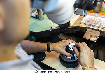 Professional jeweler working on a pieces of metal using an...