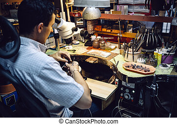 Jeweler working with optical device - Jeweler working on...