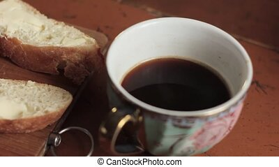 butter on a piece rural bread and cup of coffee on a wooden...
