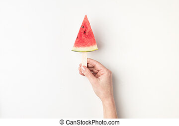 watermelon slices on stick - cropped view of peron holding...