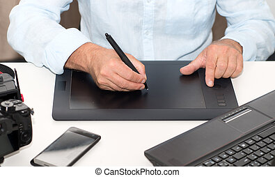 Man working on his graphics tablet, close up of hands