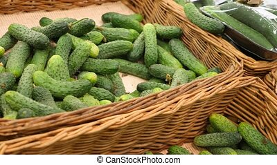 A woman in a supermarket on a vegetable shelf, buys vegetables and fruits. Man chooses cucumbers. Slow motion, 4k