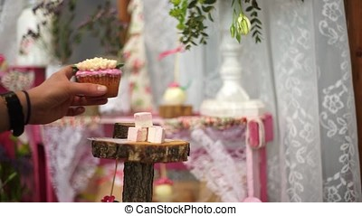 The girl puts the cupcake on the stand. Lovely decor. -...