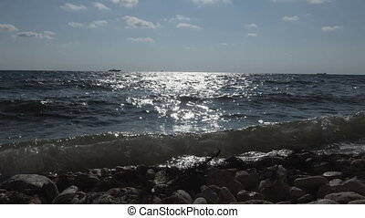 Sea shore with a small wave. Ships on the horizon in a Sunny...