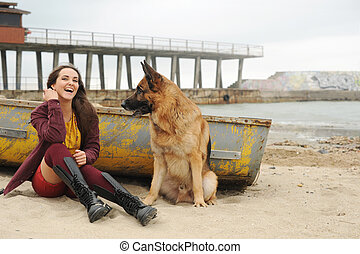 Joyful young woman have a rest with her German shepherd dog...