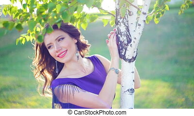 beautiful young woman near birch trees in the park.
