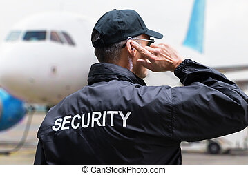 Security Guard Listening To Earpiece Against Building - Rear...