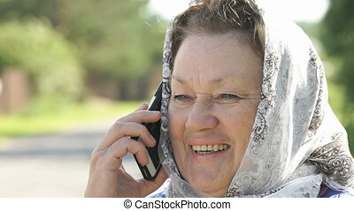 Adult woman talks on silver mobile phone outdoors - Smiling...