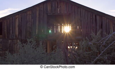 Old abandoned barn with sun light streaming through open...