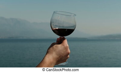 Close-up of a woman inhaling aroma of red wine on sea. Lady...