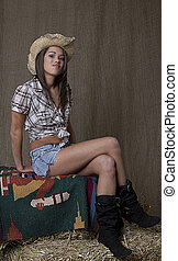 Smug cowgirl - brunette cowgirl sitting on a blankette set...