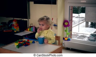 Toddler girl child drink tea with bagels at home. Static...