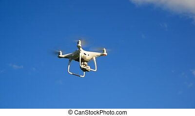 White drone flies against a sky - White quadruple flies...