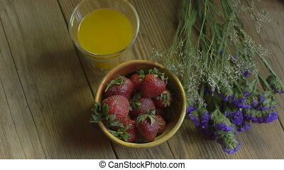 Overhead shot of ripe strawberries and a glass of fresh squeezed orange juice